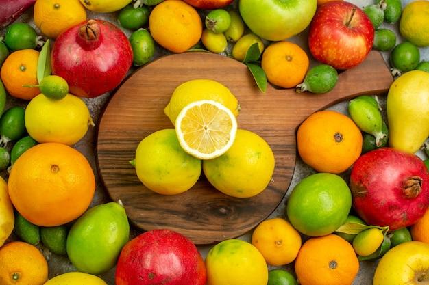 Вид сверху свежие фрукты, разные спелые и спелые фрукты на белом фоне, ягодный цвет, здоровая диета, вкусная