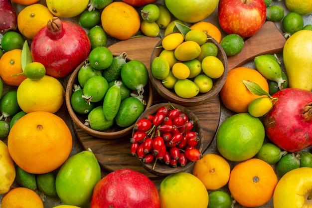 Вид сверху свежие фрукты, разные спелые и спелые фрукты на белом фоне, ягоды, вкусные здоровые цвета, диета