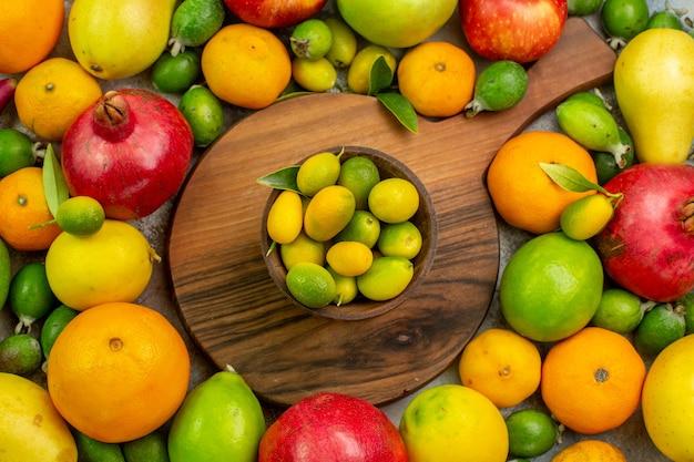 Вид сверху свежие фрукты разные спелые и спелые фрукты на белом фоне цвет ягод здоровье фото вкусная диета