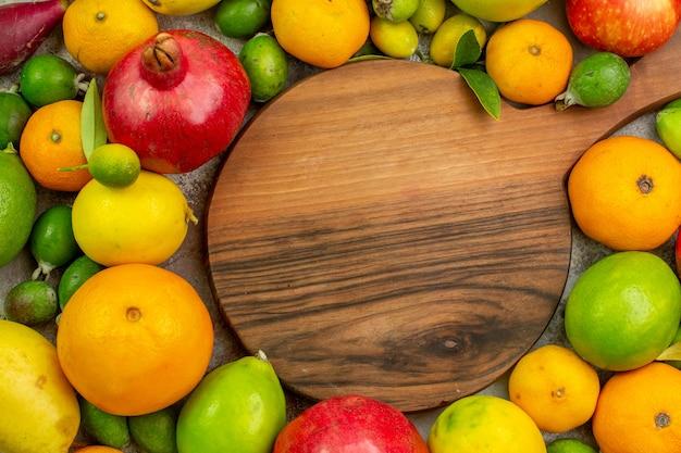 トップビュー新鮮な果物白い背景の上のさまざまな熟したまろやかな果物ベリー色おいしい健康写真