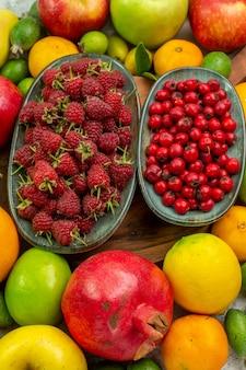 Vista dall'alto frutti freschi diversi frutti maturi e morbidi su sfondo bianco
