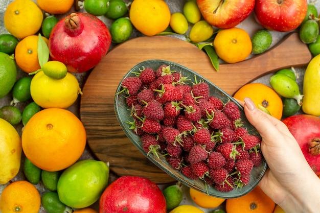 Vista dall'alto frutti freschi diversi maturi e morbidi sulla scrivania bianca