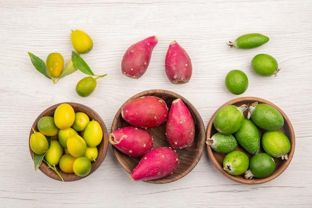 Vista dall'alto frutta fresca feijoas e altri frutti su sfondo bianco chiaro