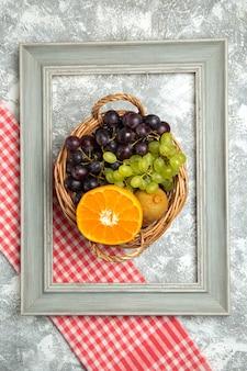 Вид сверху свежие фрукты, виноград и апельсины внутри корзины и рамки на белой поверхности, спелые спелые фрукты, свежий витамин