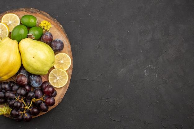 상위 뷰 신선한 과일 포도 레몬 슬라이스 자두와 어두운 배경 익은 과일 나무 식물 신선한