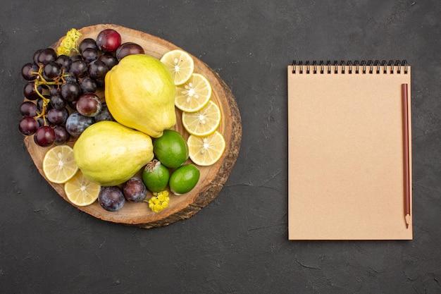Vista dall'alto frutta fresca uva fette di limone prugne e mele cotogne su superficie scura pianta da frutto fresca albero maturo