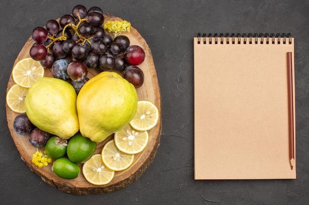 Vista dall'alto frutta fresca uva fette di limone prugne e mele cotogne su superficie scura frutti pianta fresca matura dell'albero