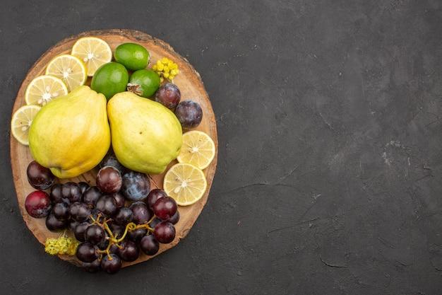 Vista dall'alto frutta fresca uva fette di limone prugne e mele cotogne su una superficie scura frutta pianta fresca matura