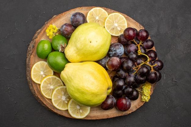 Vista dall'alto frutta fresca uva fette di limone prugne e mele cotogne su superficie scura frutti maturi pianta fresca