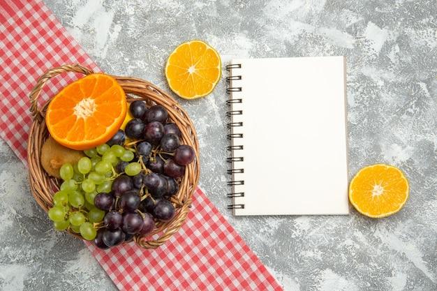 Vista dall'alto frutta fresca uva e arance all'interno del cesto su superficie bianca frutti maturi vitamine fresche morbide