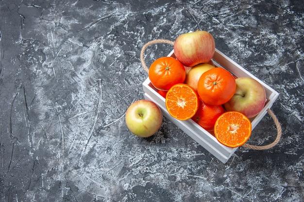 Вид сверху свежие фрукты в коробке с палочками корицы на темном фоне со свободным местом