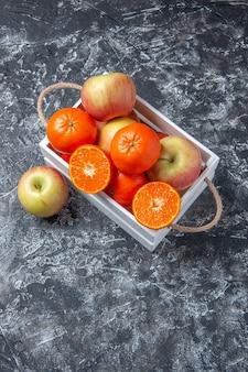 Вид сверху свежие фрукты в коробке с палочками корицы на темном фоне со свободным пространством