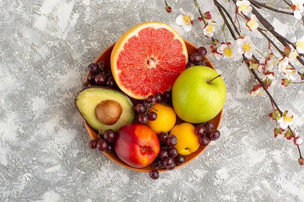 Вид сверху свежие фрукты внутри тарелки на белой поверхности