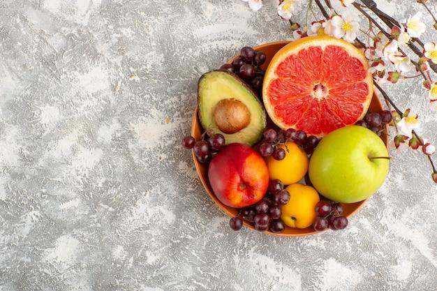 Vista dall'alto frutta fresca all'interno del piatto sulla superficie bianca