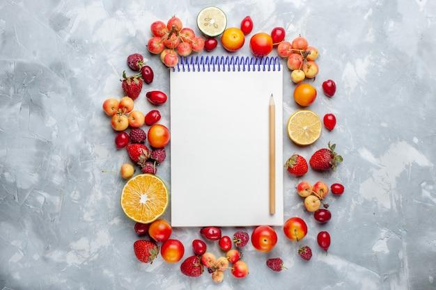 Vista dall'alto frutta fresca limoni e ciliegie con il blocco note su scrivania bianca frutta matura fresca mellow vitamina