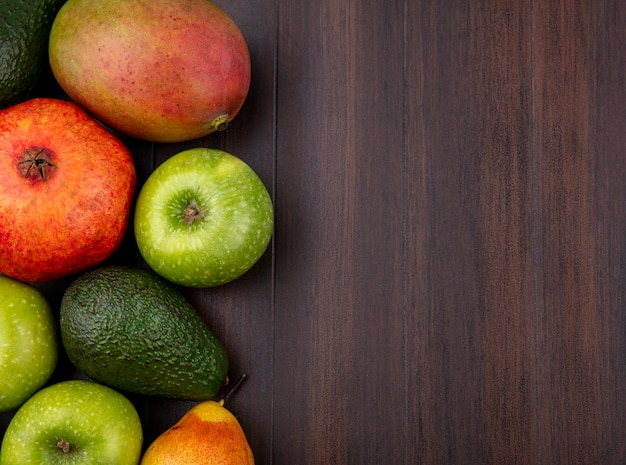 Top view of fresh fruits like pomegranate apple mango on wood with copy space