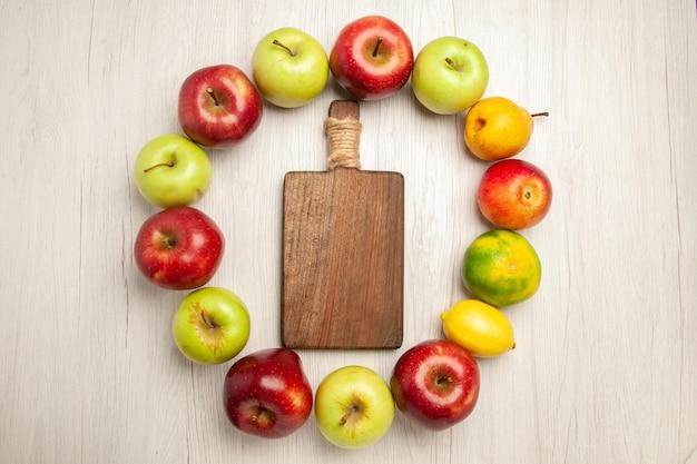 Vista dall'alto frutta fresca dolce e matura allineata su cerchio su scrivania bianca frutti vegetali color albero verde fresco