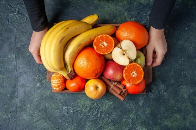 어두운 배경에 있는 여성의 손에 있는 나무 쟁반에 있는 신선한 과일 오렌지 만다린 사과 바나나와 계피 스틱
