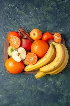 어두운 배경의 여유 공간에 있는 나무 쟁반에 있는 신선한 과일 오렌지 만다린 사과 바나나와 계피 스틱
