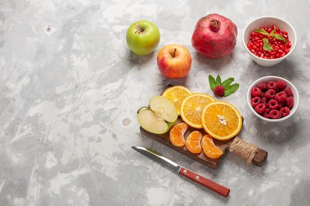 Вид сверху свежие фрукты апельсины малина и гранаты на белой поверхности фруктовый свежий мягкий витаминный сок тропическая экзотика