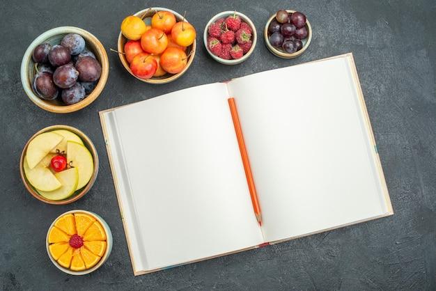 トップビュー新鮮な果物プラムリンゴと暗い背景に他の果物熟したまろやかな新鮮な果物の健康
