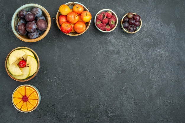 Top view fresh fruits plums apples and other fruits on a dark background mellow fresh fruit health ripe