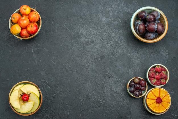 Vista dall'alto frutta fresca prugne mele e altri frutti sullo sfondo scuro frutta fresca matura e dolce salute