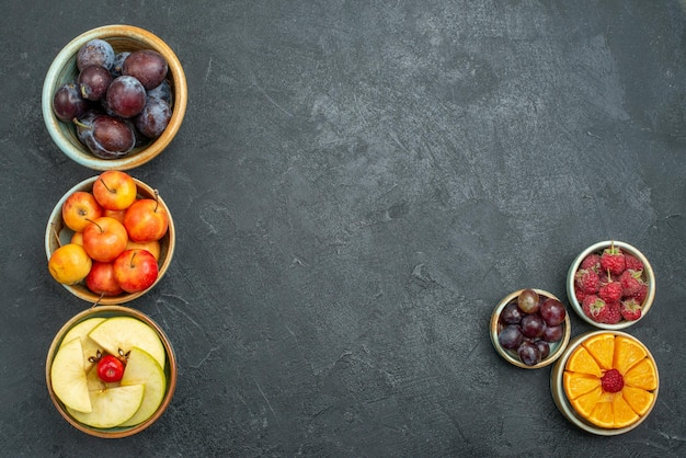 Top view fresh fruits plums apples and other fruits on dark background ripe mellow fresh fruit health