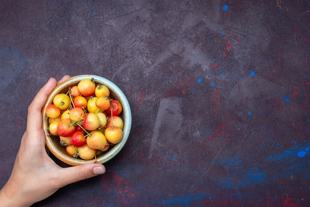 Top view of fresh fruits plums inside plate on the dark surface