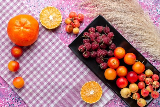 Top view of fresh fruits raspberries and plums inside black form with oranges on the pink surface
