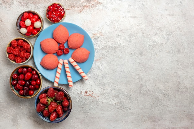 Vista dall'alto frutta fresca lamponi fragole e cornioli con i biscotti su uno spazio bianco
