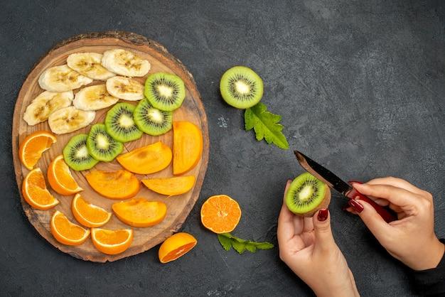 Vista dall'alto di frutta fresca su un vassoio di legno che taglia a mano una fetta di kiwi su sfondo scuro
