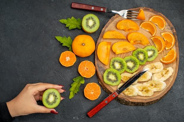 Vista dall'alto di frutta fresca messa su un vassoio di legno mano che tiene un'arancia sul tavolo nero