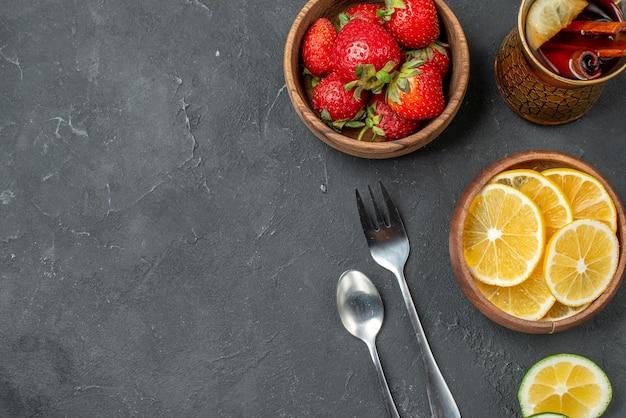 灰色の表面に新鮮な果物のイチゴとレモンの上面図