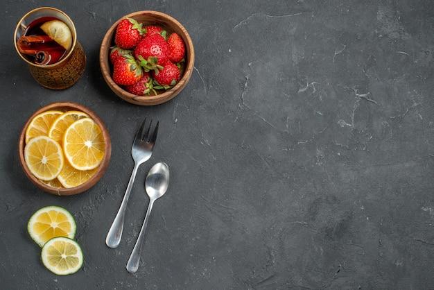 Вид сверху свежие фрукты клубники и лимоны на серой поверхности