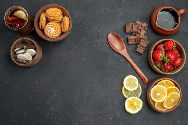 灰色の表面にクッキーと新鮮な果物のイチゴとレモンの上面図
