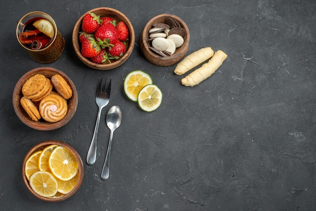 Top view fresh fruits strawberries and lemons with cookies on gray surface