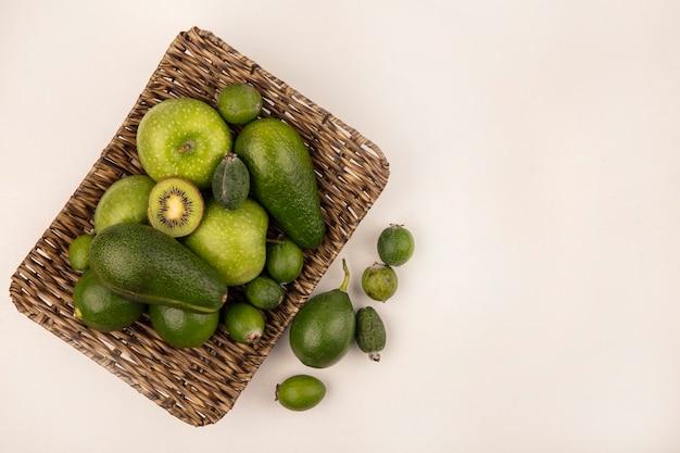 Vista dall'alto di frutta fresca come avocado feijoas mela verde su un vassoio di vimini su un muro bianco con spazio di copia