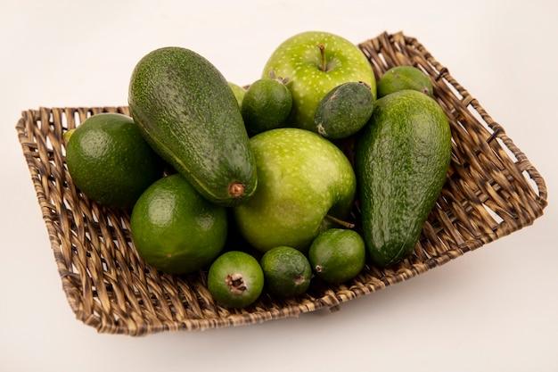 Vista dall'alto di frutta fresca come avocado feijoas mela verde su un vassoio di vimini su un muro bianco