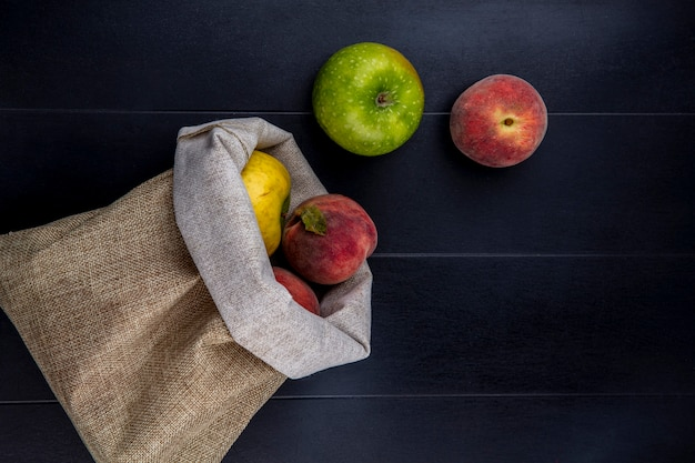 Top view of fresh fruits such as green apples and delicious peaches in a burlap bags on black