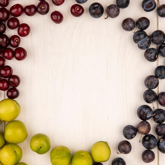 Vista dall'alto di frutta fresca come ciliegie verdi plumcherries e prugnole isolate su uno sfondo di legno bianco con spazio di copia
