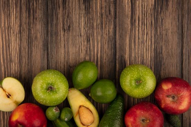 Vista dall'alto di frutta fresca come mele verdi e rosse feijoas limes avocado isolato su uno sfondo di legno con spazio di copia