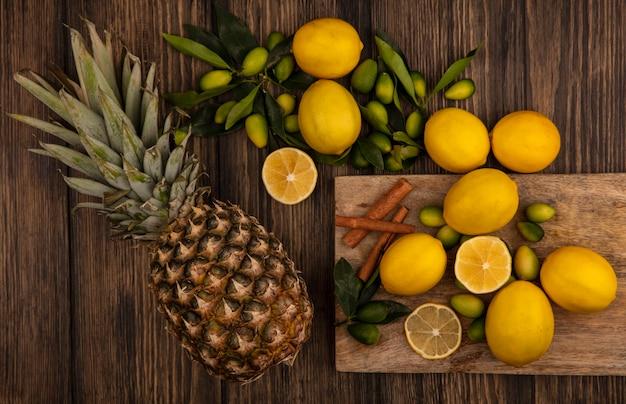 Vista dall'alto di frutta fresca come kinkan e limoni con bastoncini di cannella su una tavola da cucina in legno con ananas su una superficie di legno