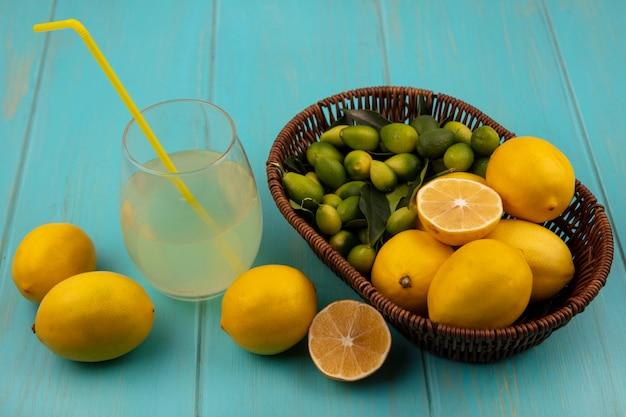 Vista dall'alto di frutta fresca come limoni e kinkan su un secchio con succo di limone fresco in un bicchiere con limoni isolato su una parete di legno blu