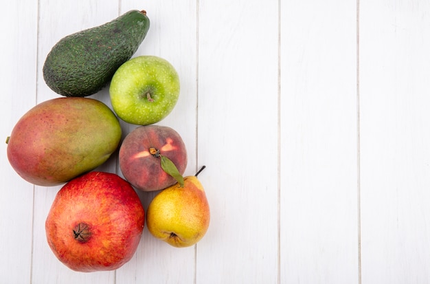 Top view of fresh fruits such as mango pear apple pomegranate on white with copy space