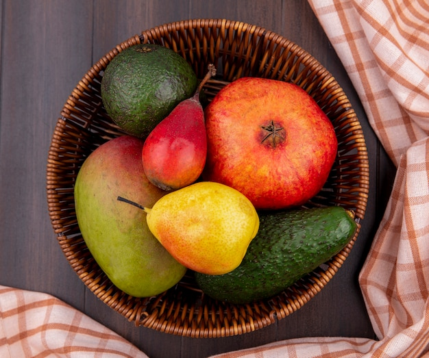Top view of fresh fruits such as pear lemon mango pomegranate on bucket with checked tablecloth on wood