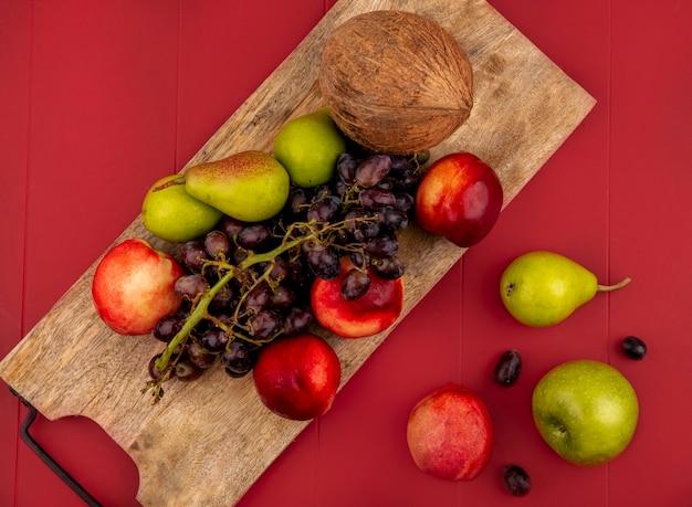 赤い背景の上の木製のキッチンボード上のpeargrapepeachなどの新鮮な果物の上面図