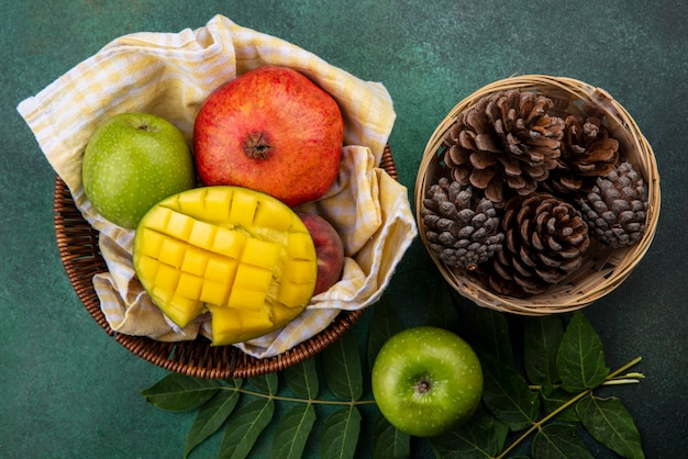 Top view of fresh fruits such as sliced mango pomegranate apple on bucket with pine cones on bsuket on green