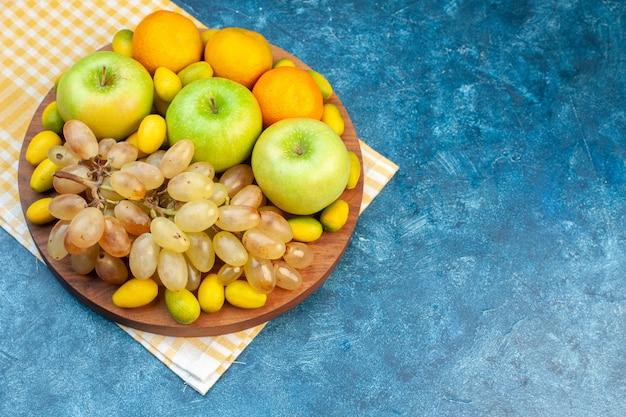 上面図新鮮な果物みかんリンゴと青いテーブルの上のブドウ