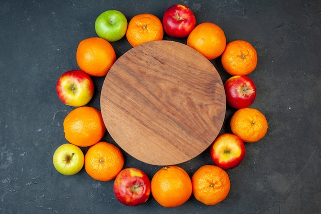 Top view fresh fruits tangerines oranges bananas and apples on dark background